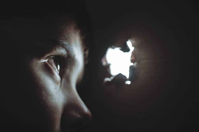 Eye peering through hole