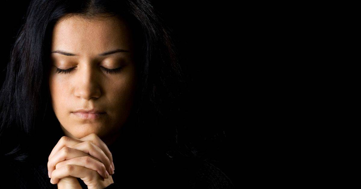 Woman praying with hands folded