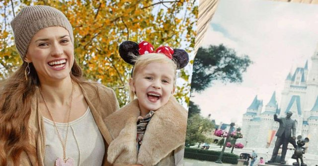Mother laughing with young daughter who is wearing mickey mouse ears