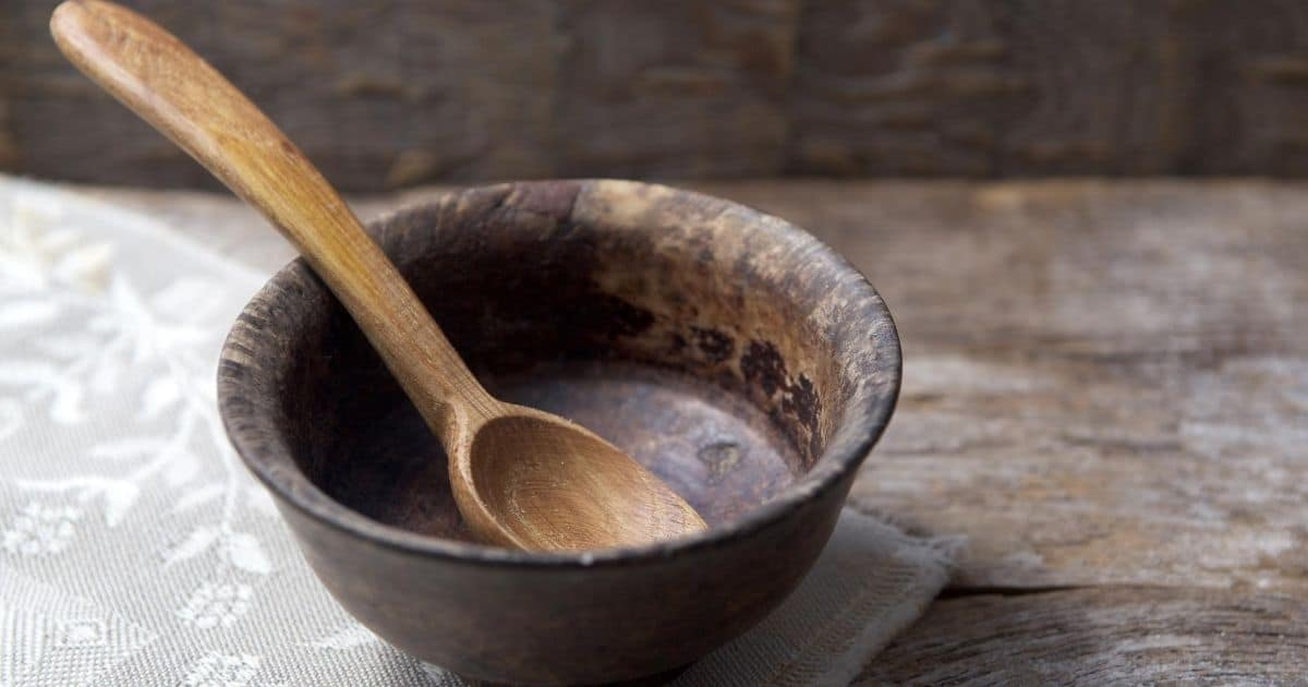 Empty wooden bowl and spoon, for types of fasting in the Bible
