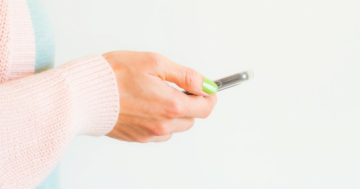 Woman scrolling social media on her cell phone