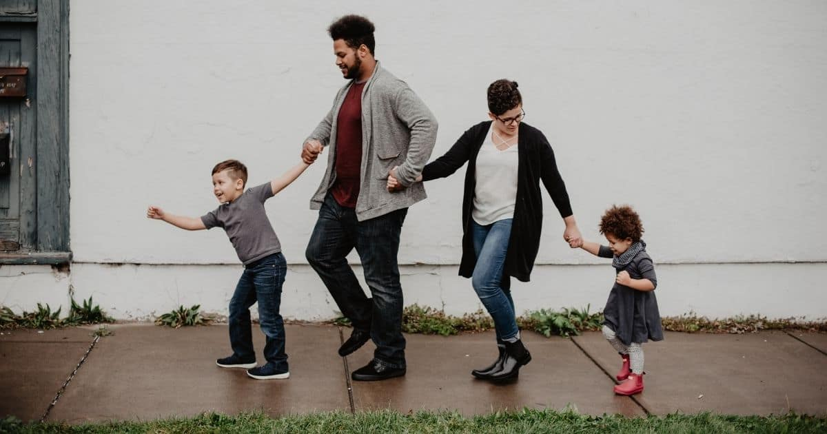 Young family walking down a sidewalk together