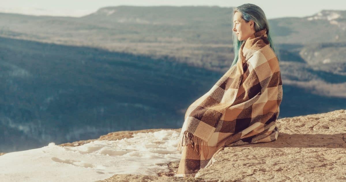 Woman sitting outside enjoying nature, detoxing from social media