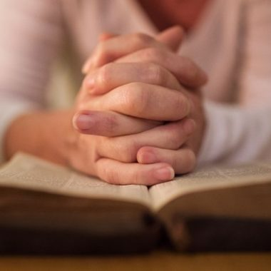 praying with hands folded on bible